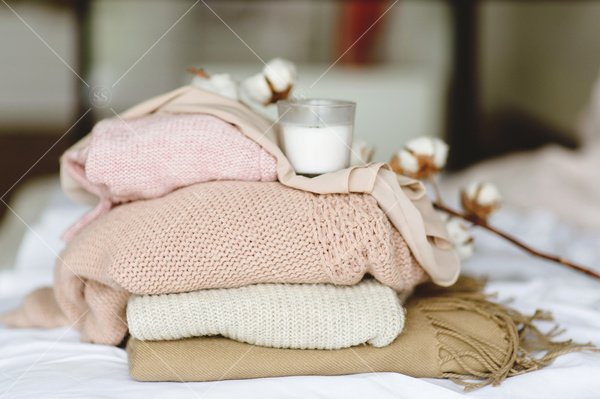 sweaters folded on bed