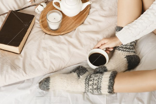 woman in bed with tea and book