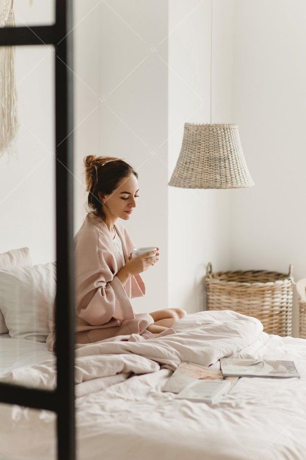 woman drinking tea in bedroom