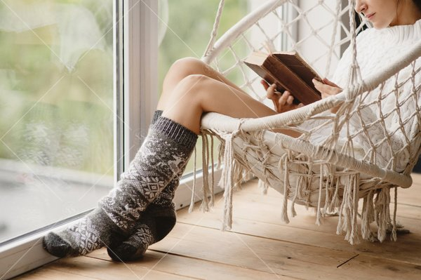 woman reading book in hanging chair by window