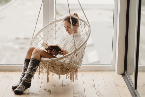 woman reading in hanging chair