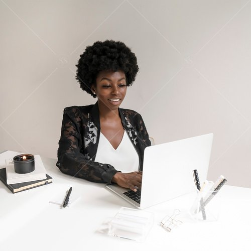 woman of color working on laptop at desk
