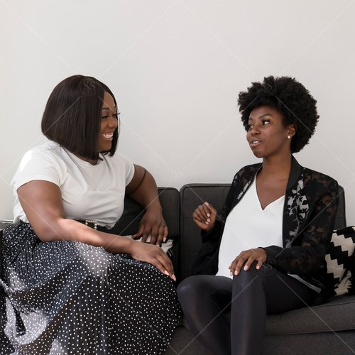 two women of color chatting on sofa