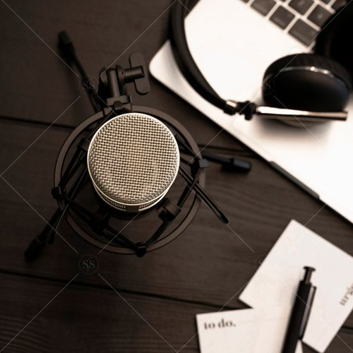 workspace with laptop, microphone, headphones