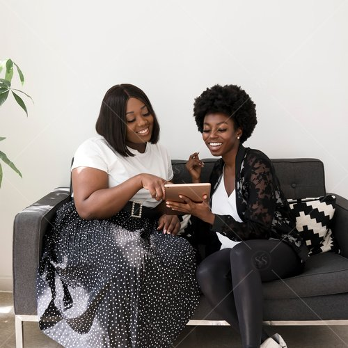 women of color working together on sofa