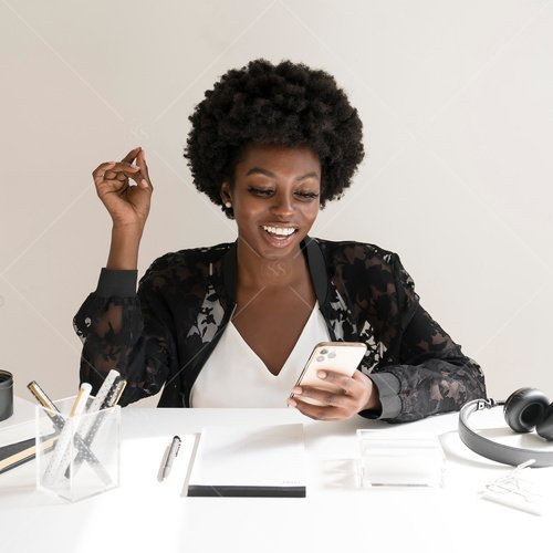 woman of color looking at phone at desk