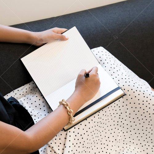 woman of color writing on sofa