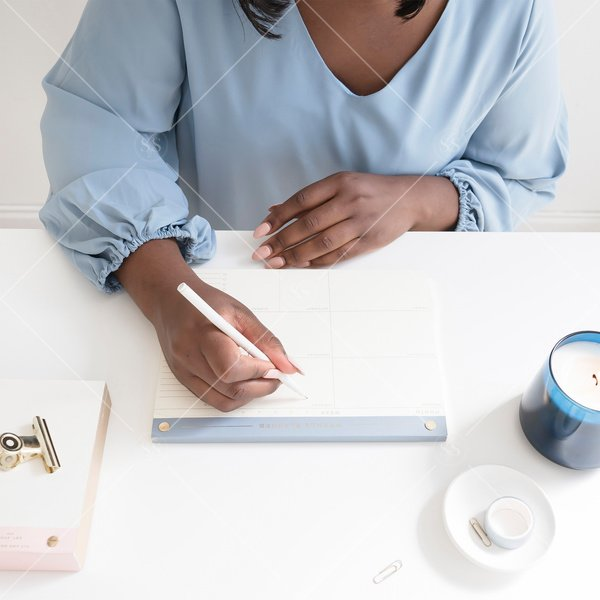 woman of color writing at desk