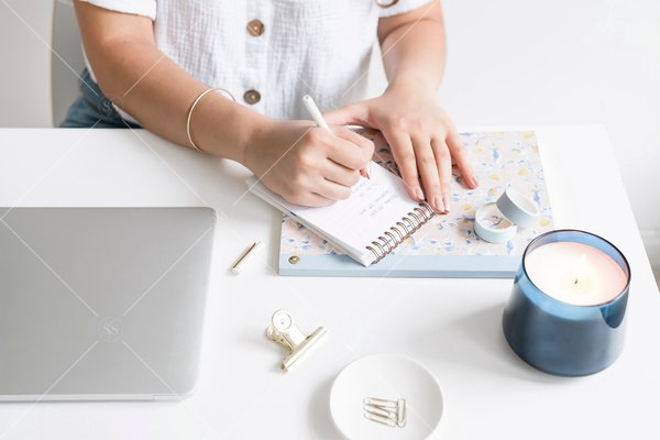 woman writing on notebook at desk