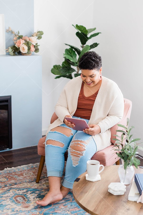 woman of color working on tablet from living room