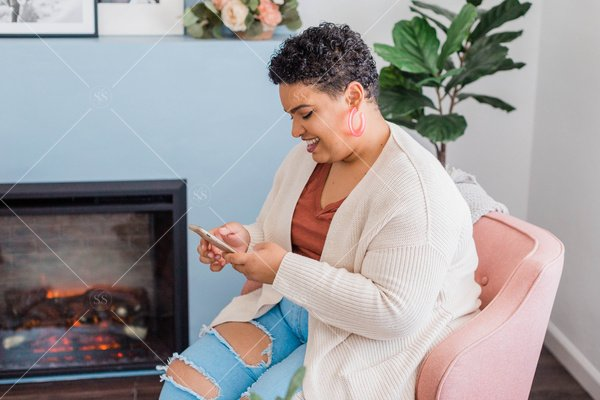 woman of color looking at phone in front of fireplace