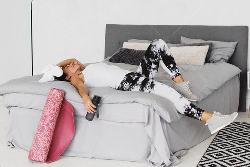 woman resting on bed after workout
