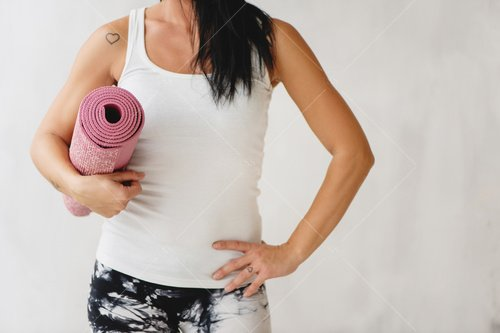 woman holding yoga mat