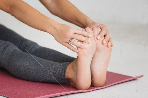 closet up of woman stretching on yoga mat