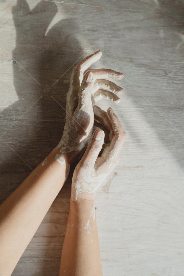 hands covered in clay stock photo