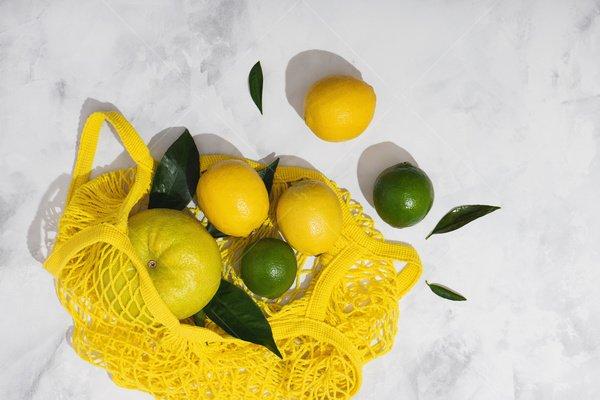 lemons, limes and grapefruit in market bag stock photo