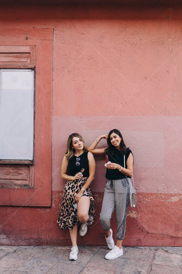 friends posing by wall stock photo