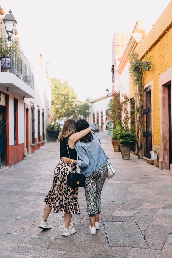 friends hugging in street stock photo