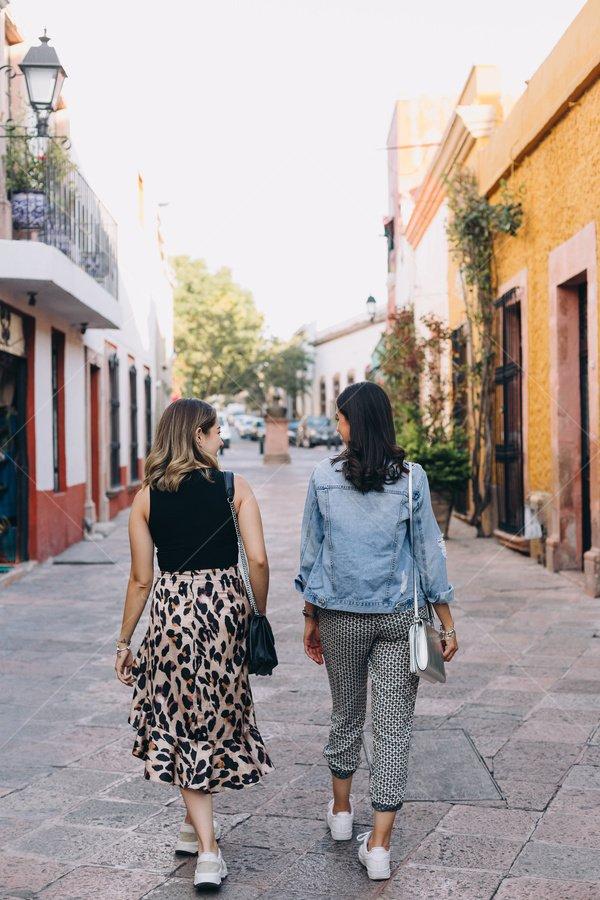friends walking down street stock photo