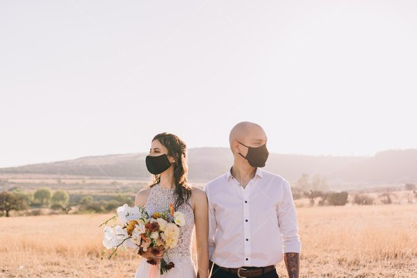 bride and groom in face masks stock photo