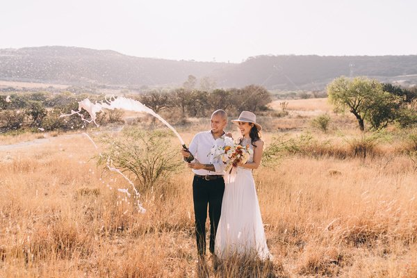 bride and groom popping champagne stock photo