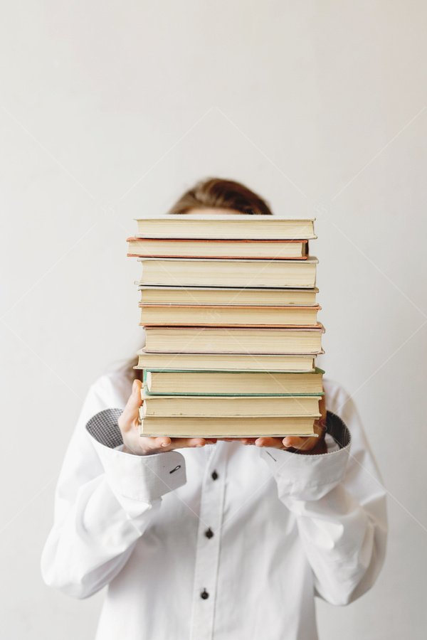 woman holding stack of books stock photo