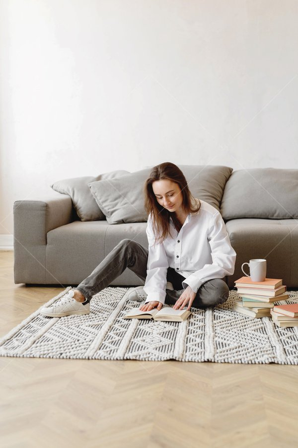 woman reading in living room stock photo