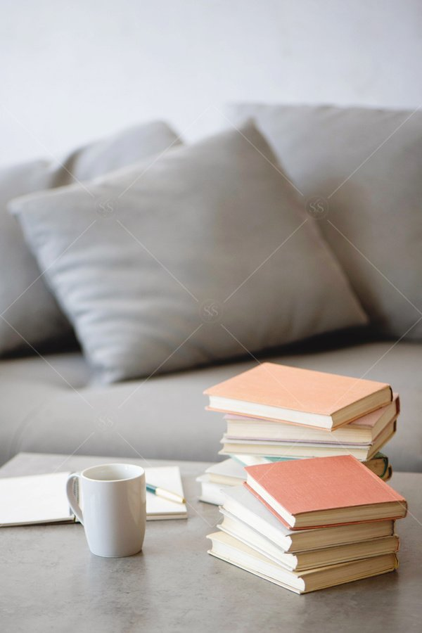 piles of books in living room stock photo