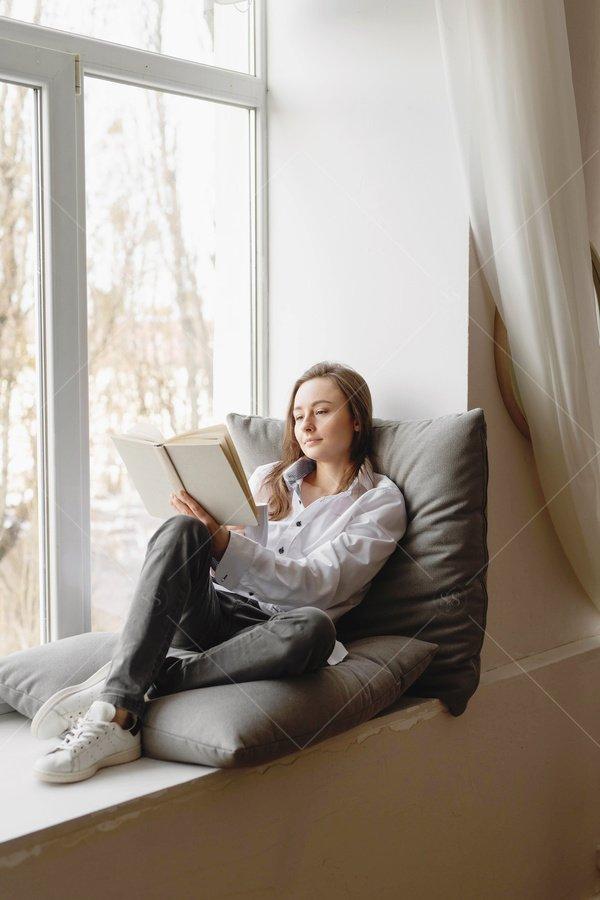 woman reading on window seat stock photo