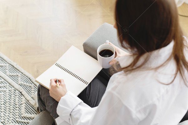 woman writing in notebook over coffee stock photo
