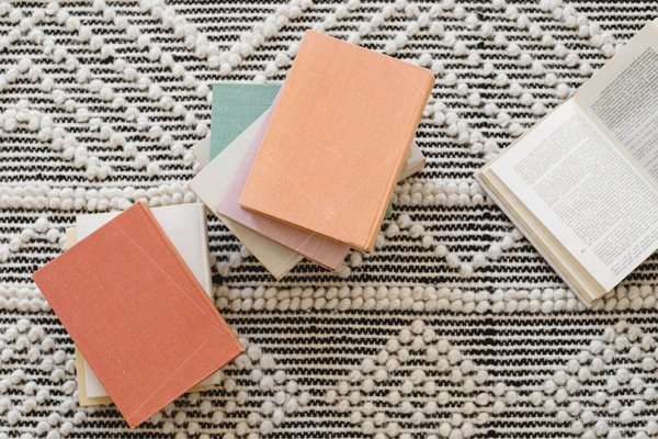 piles of books on rug stock photo