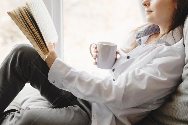 woman reading book and drinking coffee stock photo