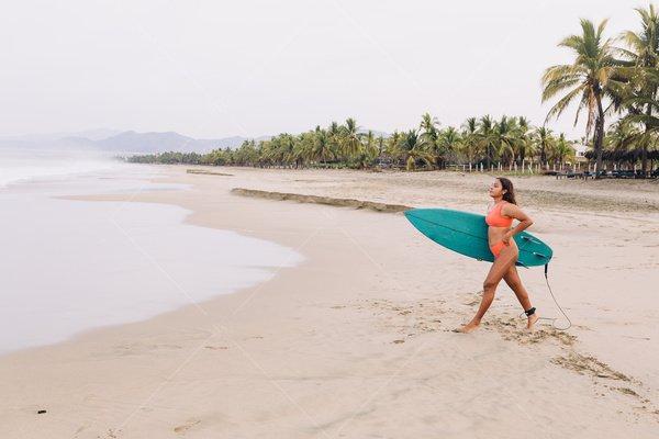 Latina woman surfing stock photo