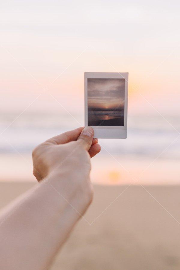woman holding sunset photo at beach stock photo