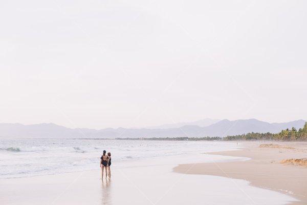 women standing on beach stock photo