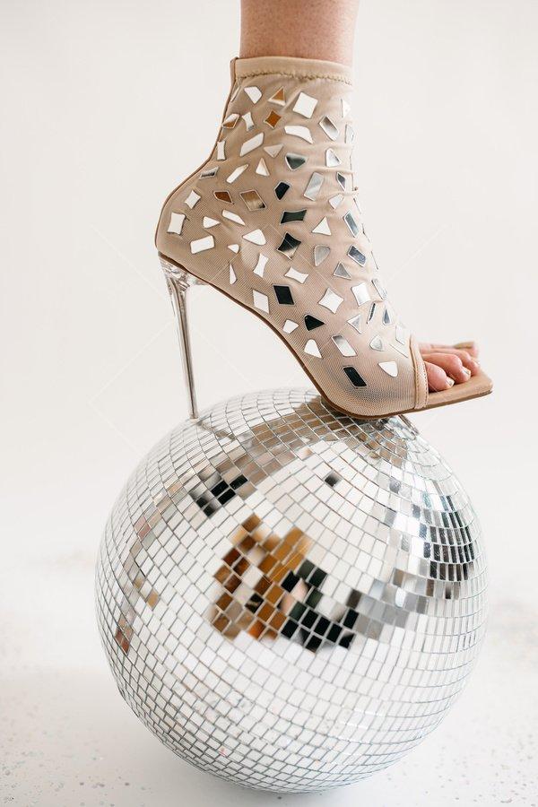 standing on disco mirror ball stock photo