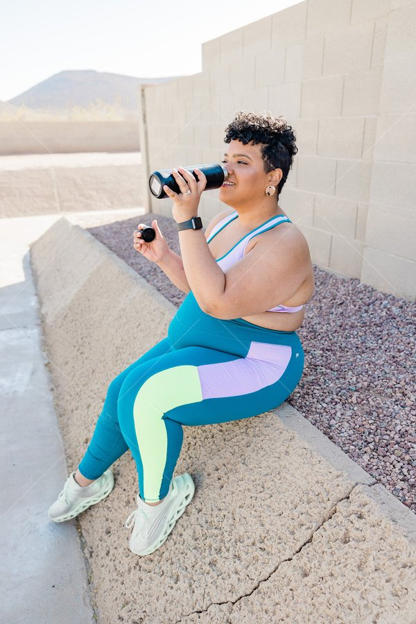 plus size woman of color post workout water break stock photo