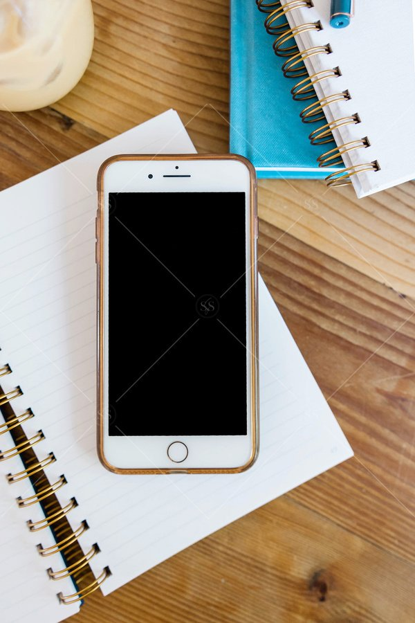 iphone mockup on desk with notebooks stock photo