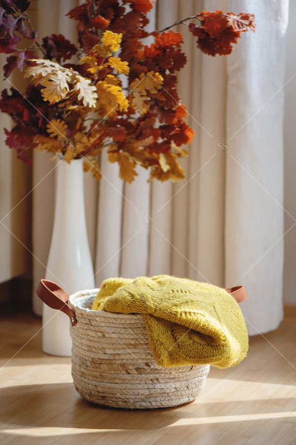 sweater in basket with fall leaves stock photo
