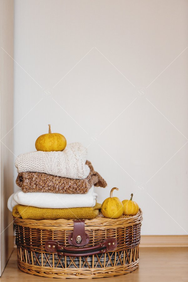 fall home decor basket sweaters and pumpkins stock photo