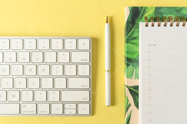 flat lay of a keyboard, pen, notebook, and blank to do list against a yellow backgroun