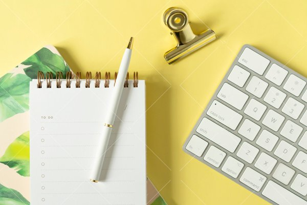 flat lay against a yellow background with keyboard, notebook, blank to do list, pen, and binder clip