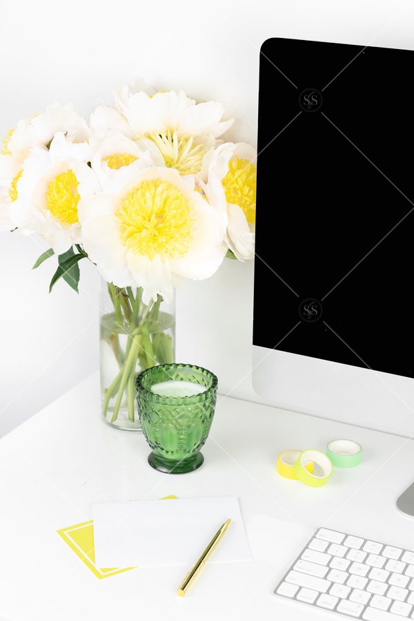 desk with computer and flowers