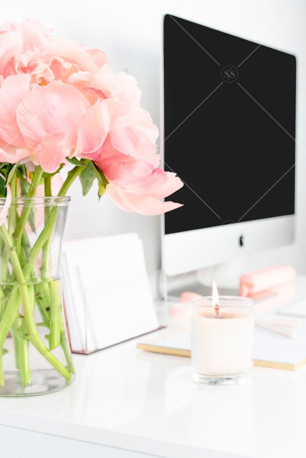 computer mockup sitting on desk with flowers and candle