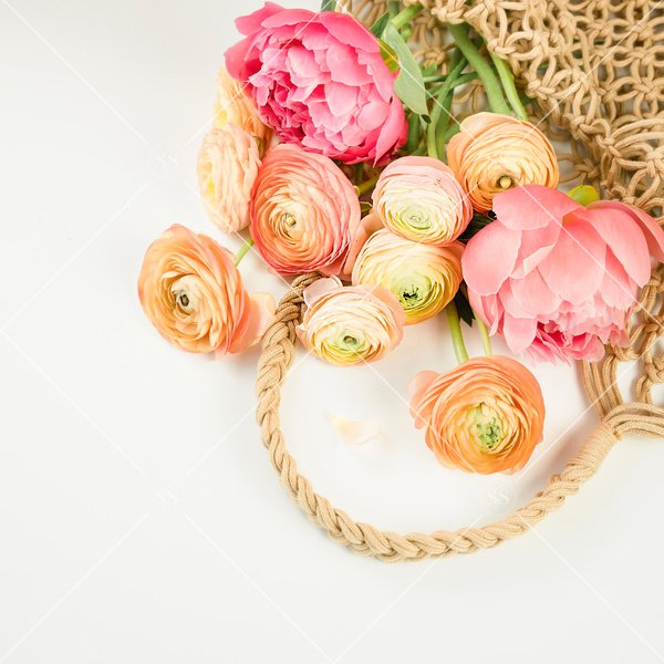peonies and ranunculus in a woven bag