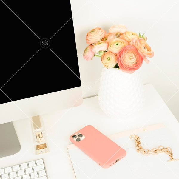 Coral ranunculus flowers on a white desktop.