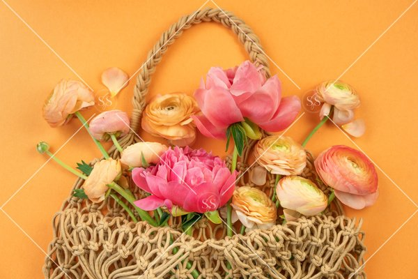 Peonies and ranunculus in a reusable woven bag.