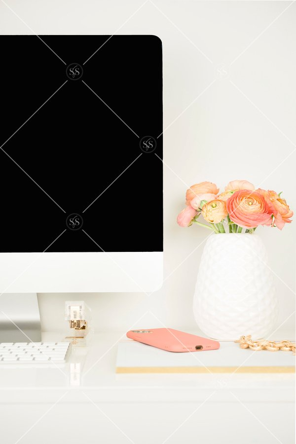 Coral ranunculus in a white vase on a desk with iMac computer.
