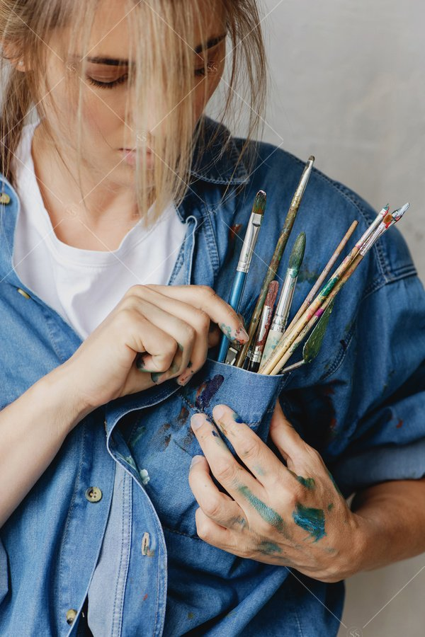 artist with paintbrushes in her pocket