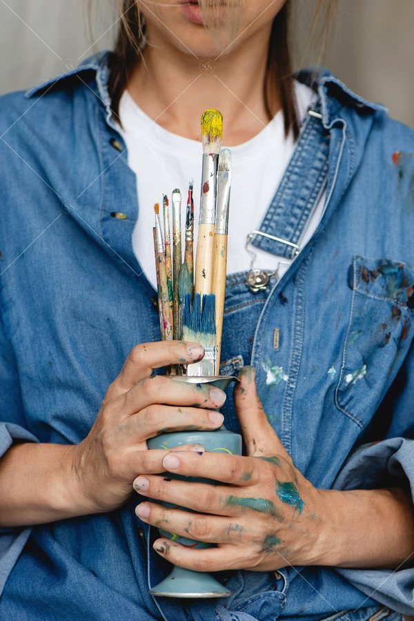 artist holding paint brushes in vase